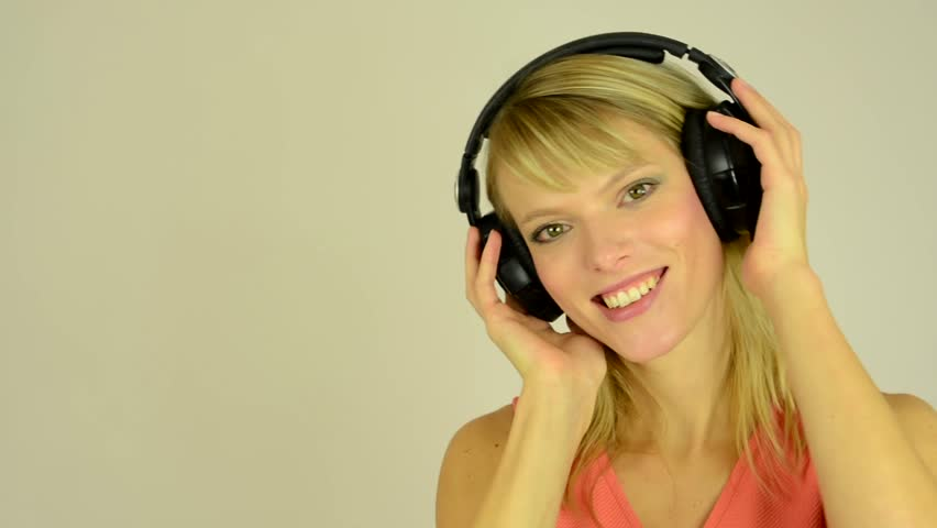 Young attractive woman listens to music with headphones and dancing - studio - closeup (hands hold headphones) - closeup | Shutterstock HD Video #7941379