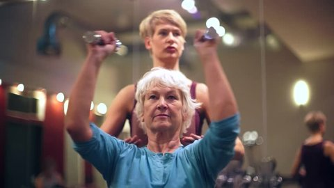 Senior women with fitness trainer in gym lifting barbells for pectoral training as sport exercise