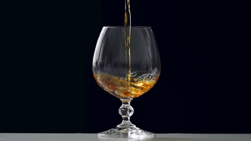 Close up of brandy being poured into snifter against black background