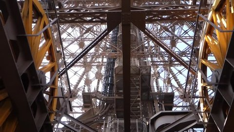 Paris, Eiffel Tower. Camera on second level looking up through large yellow cable drums for elevator mechanism.
