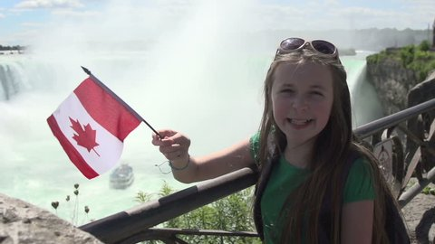 A mid-shot of a young girl on vacation, smiling and waving a Canadian flag at Niagara Falls, in slow motion.
