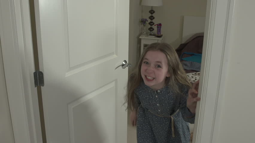 A mid-shot of a young girl running upset into her bedroom. She shouts at camera before slamming the door.