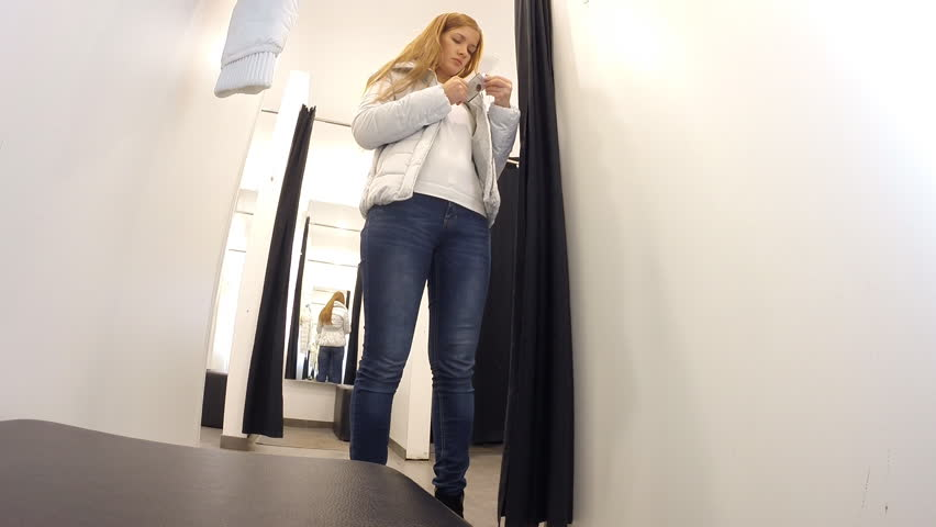 Ufa - OCT 13: The girl measures the jacket at the store YNG on October 13, 2013 in Ufa, Russia. The first company store YNG in Russia was opened in 2009  | Shutterstock HD Video #7979359