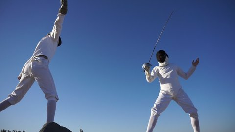 A man and woman fencing on the beach. - Slow Motion - Model Released - 1920x1080 - HD - filmed at 59.94 fps