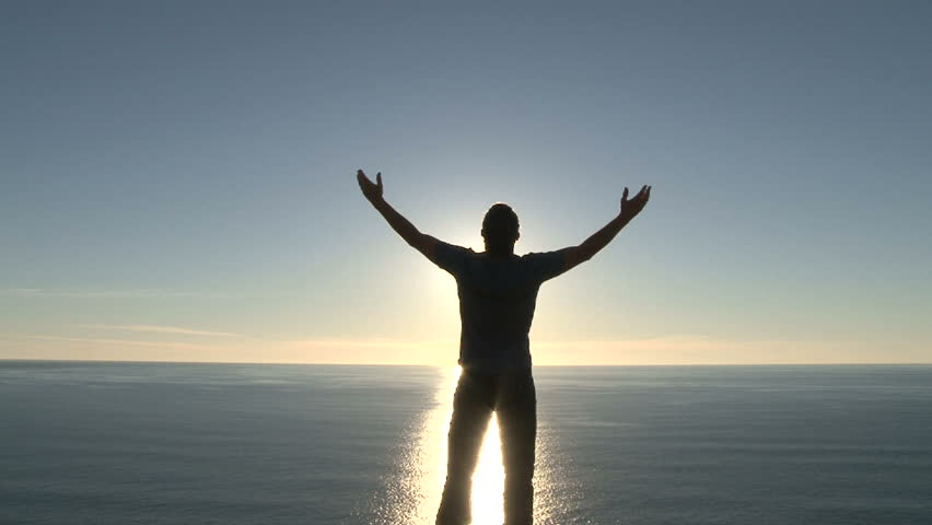 Model released man raising his arms, enjoying a beautiful sunny day high above the Pacific Ocean in Oregon. | Shutterstock HD Video #8029438