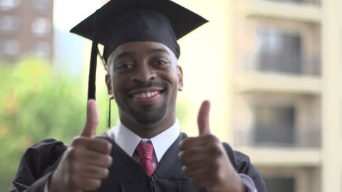 A close-up of a black man, dressed for graduation. He turns to camera and gives a thumbs-up of excitement.
