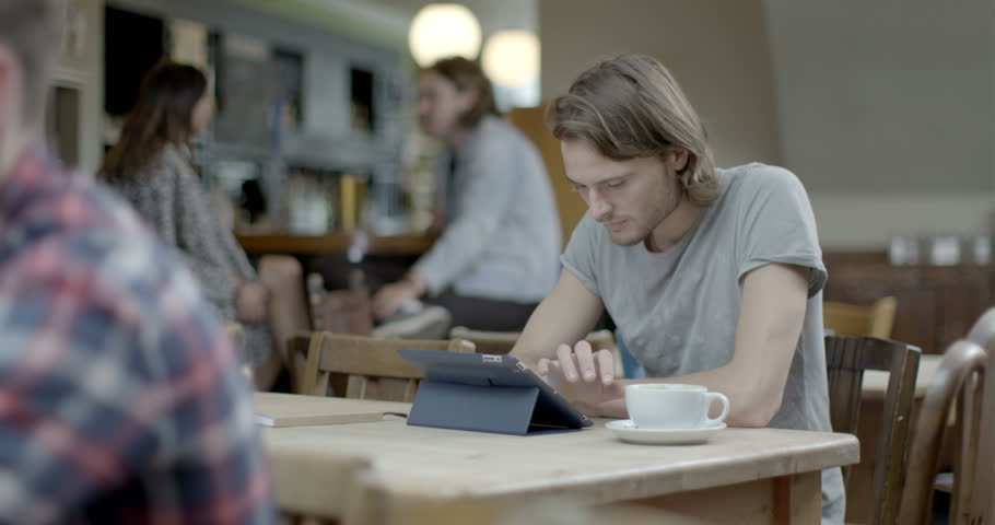 Man using digital tablet and drinking coffee while sitting in pub   Shutterstock HD Video #8044387