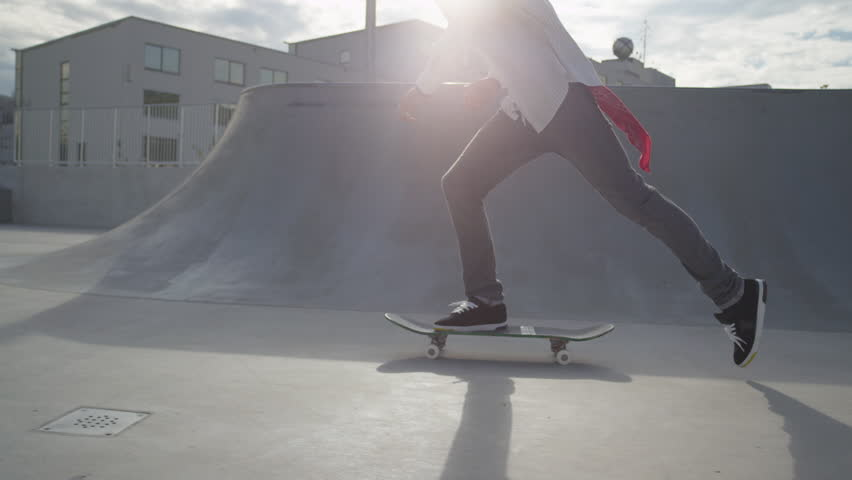 SLOW MOTION: Skateboarder jumps on his skate and starts cruising #8060719