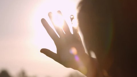 Girl looks at the sun through her hand