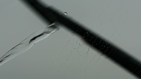 Slow motion view of windshield wiper movement in rain and water dropping.