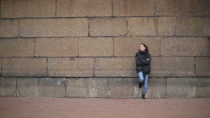 Long shot of the girl near the stone wall of Peterhof #8111869