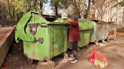 Homeless woman is searching for food in garbage dumpster/Woman in poverty/Woman in poverty is searching something in container.
