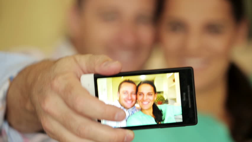Happy couple taking selfie photo with cellphone on sofa at home  | Shutterstock HD Video #8154376