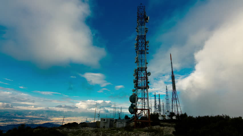4K big tall communication towers with blue sky and clouds. Communication and broadcast towers shot from the top of mount Imettus in Athens at the broadcasting antennas and towers area.   Shutterstock HD Video #8179399