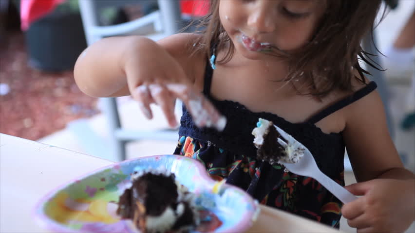 a cute little girl eating birthday cake