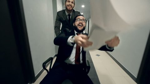 Guys celebrating a deal riding a chair in the office hall and tossing documents