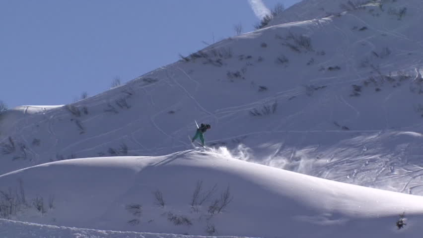 A skier jumps, spins in mid air before falling on snow while landing, pan shot | Shutterstock HD Video #8253343