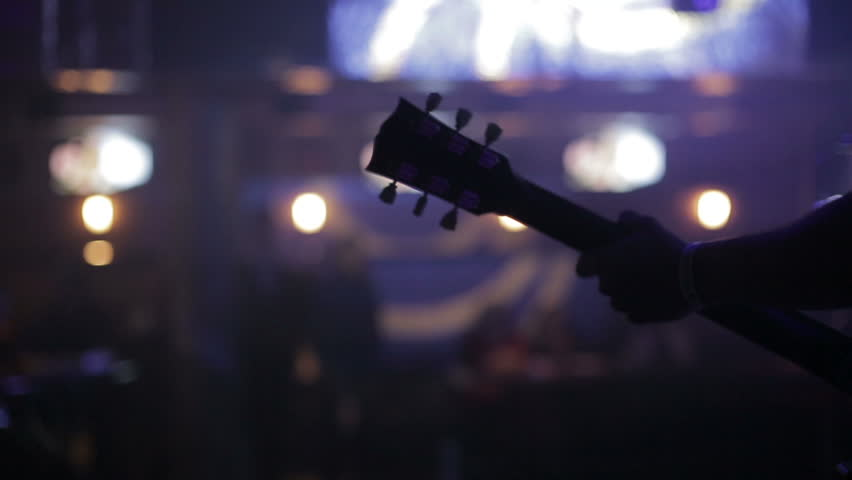 Man lead guitarist playing electrical guitar.Concert rock band performing on stage with singer performer, guitar, drummer. Music video punk, heavy metal or rock group.   Shutterstock HD Video #8268622