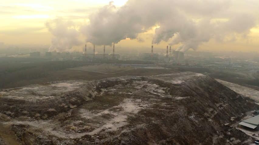 Polluting factory at dawn,aerial vew, near the dump
