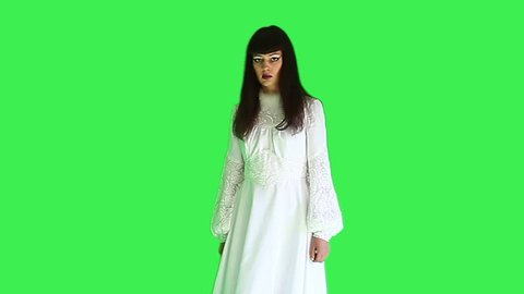 Horror concept - woman in white dress on green screen.