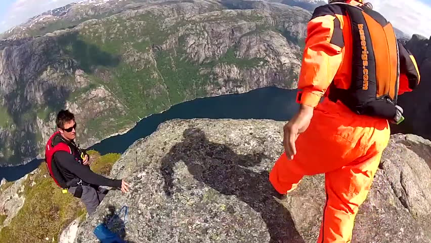 Two base jumpers leaps off from a cliff before gliding down in the air over a river, POV
