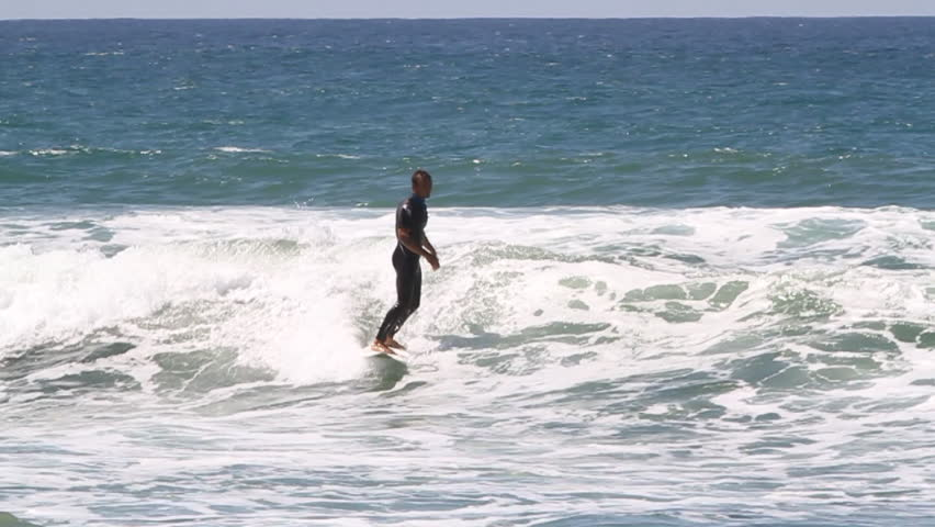 A surfer riding a small wave, tries to maintain balance but loses and falls into water | Shutterstock HD Video #8303449