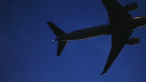 Low angle slow motion view of an airplane silhouette flying overhead flashing red lights in dark sky. Modern twin jet about to land at night.