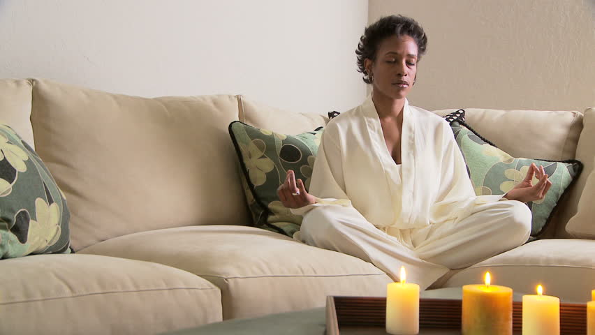 Woman on sofa meditating with candles