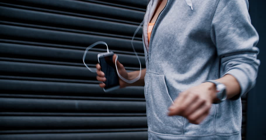 Woman Runner running with smartphone in her hand and listens to music through earphones in slow motion