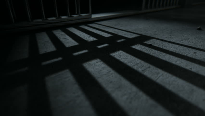 A static camera closeup showing a dimly lit floor of a prison cell and the cast shadows of the door slamming shut