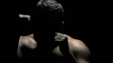 Boxing in the Dark - Caucasian Boxer Spars, Throwing Punches on Black Background