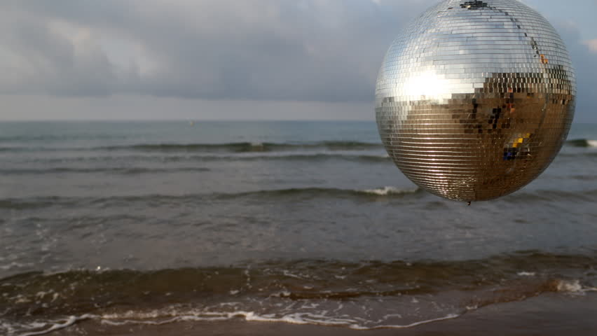 4k shot of funky large discoball spins during sunrise on the beach with the sea in the background. useful for vj loops, events, clubs and parties