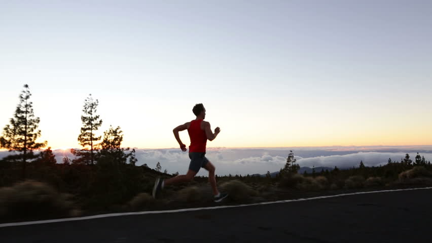 Runner man sprinting running fast on road at sunset. Male athlete sprinter running at speed on mountain road training for marathon living healthy active lifestyle in nature.