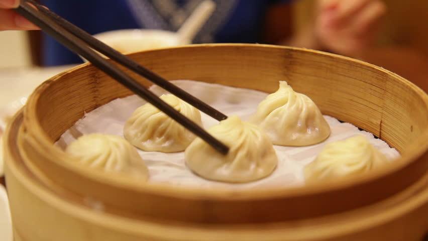 Xiao long bao / xiaolongbao soup dumplings. Woman eating Chinese Shanghainese steamed dumpling buns with chopsticks in restaurant in China.
