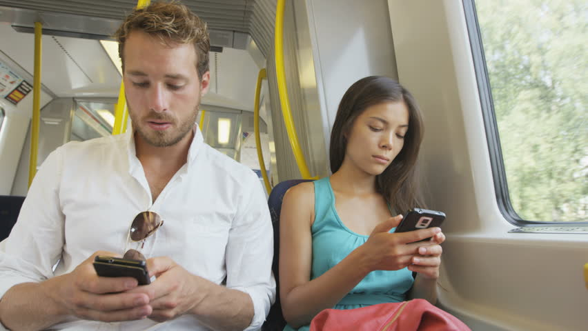 Passengers commuting using smartphones 4g wireless internet network sms texting or working while commuting to work in train. Multiracial Asian woman and Caucasian man on smart phone on commute to work | Shutterstock HD Video #8454907