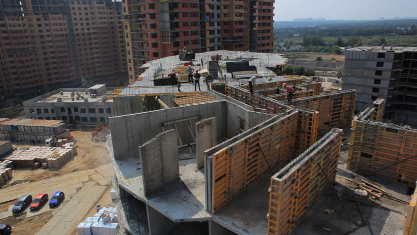 Construction industry. Aerial shooting.Camera flies over unfinished house. Builders are working on the roof