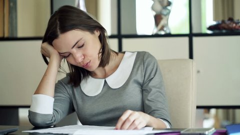 Tired businesswoman with documents yawning and sleeping by desk at home