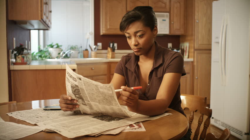 An African American woman performs various tasks around the house. She searches for a job, pays bills, makes coffee, studies the bible, reads a book, and works on her laptop.