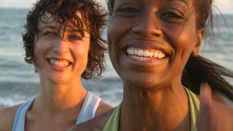 Portrait of two young women at beach during sunset