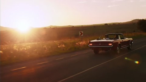 Couple driving classic cherry red convertible cabriolet car, steadicam shot with sun flare.