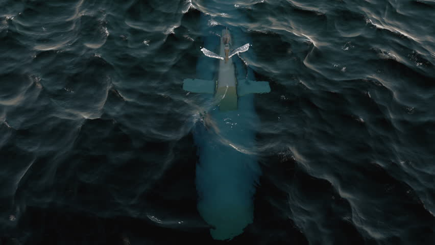 Submarine patrolling just below the water's surface at periscope depth