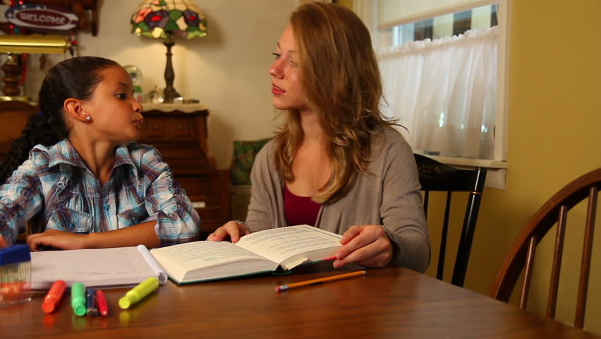 A young girl gets help with her homework.
