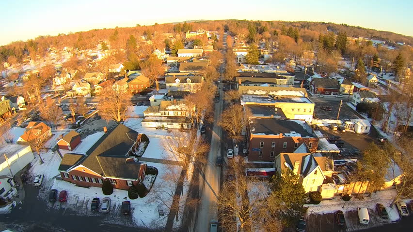 Millbrook, NY -Circa 2015: Aerial winter sunset over cute upstate NY village, evening cold sets in as light fades over main street with traffic below.
