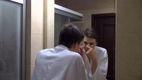 Teenage boy squeezing out pimples, face, mirror, acne, zits, spots, care