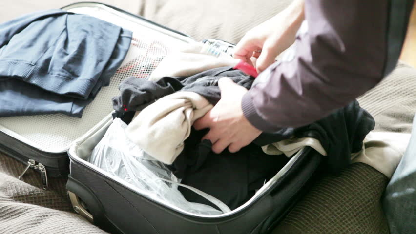 Man thrown clothes and toothbrush in suitcase and pulled out of it | Shutterstock HD Video #8599609