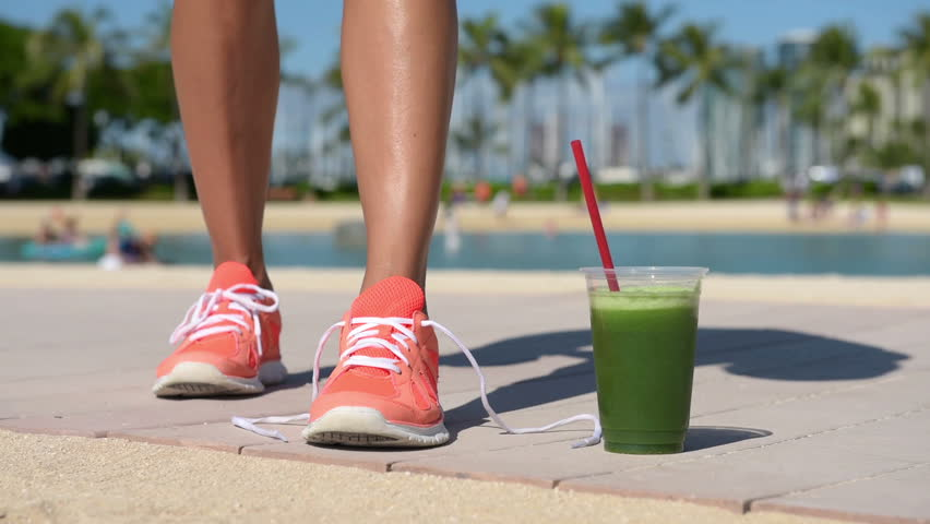 Running woman with green vegetable smoothie. Fitness runner and healthy lifestyle concept with female model tying running shoe laces.
