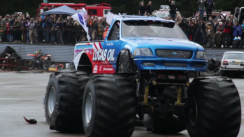 Huge Bigfoot truck running over junk cars, stunt, performance. Monster auto show demonstration, entertaining people outdoor, extreme power, destruction activity. Big wheel transport, driving hobby