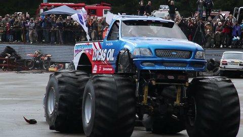 Huge Bigfoot truck running over junk cars, stunt, performance. Monster auto show demonstration, entertaining people outdoor, extreme power, destruction activity. Big wheel transport, driving hobby