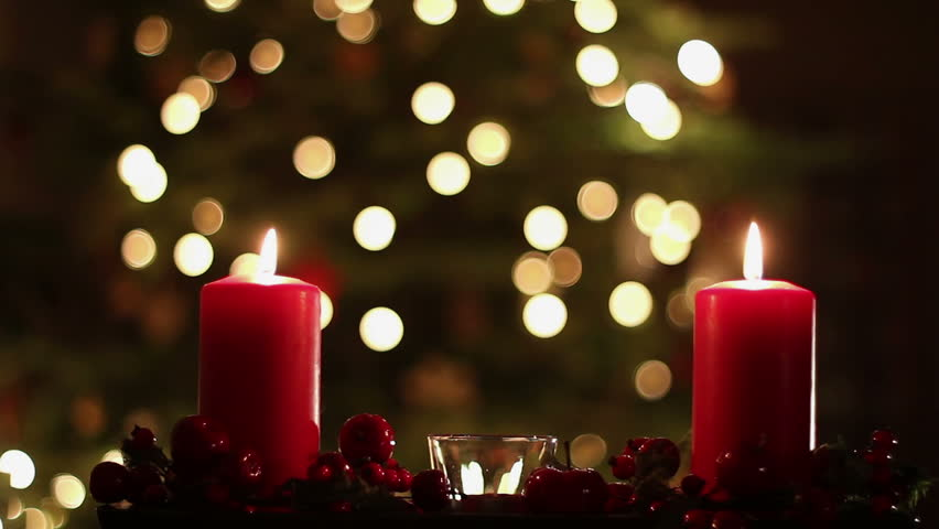 Female Hand Lighting A Candle Christmas Tree In The Background
