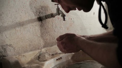 Guy approaches a dirty clogged sink, leaves down used syringe after taking dose of heroin and washed hands and face, then he closes tap and leaves. Tilt up. Close up. Drug addiction. Narcotic. Junkie.
